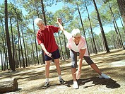Active senior couple in sportswear exercising, woman stretching, man assisting tilt