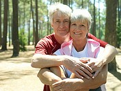 Senior couple in sportswear sitting in wood, man embracing woman, smiling, front view, portrait