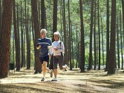 Senior couple in sportswear jogging through woodland, smiling