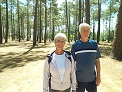 Senior couple in sportswear standing in clearing in wood, smiling, front view, portrait