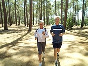 Senior couple in sportswear jogging through woodland, smiling, front view, portrait