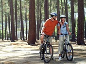Senior couple in cycling helmets sitting on bicycles in wood, side by side, portrait