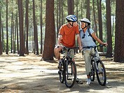 Senior couple in cycling helmets sitting on bicycles in wood, side by side, smiling