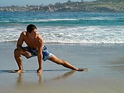 Man in swimming shorts stretching leg on sandy beach, sea in background