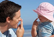 Father and daughter 2-4 playing on beach, touching noses with fingers, smiling, side view