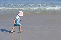 Girl 2-4 in pink sun hat walking on sandy beach near water's edge, profile