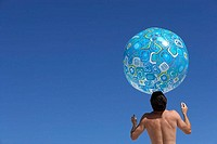 Man balancing large turquoise beach ball on head, rear view