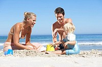 Two generation family building sandcastles on sandy beach, smiling