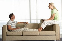 Couple relaxing on sofa at home, face to face, man using laptop, woman reading book, profile