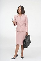 Portrait of a businesswoman holding a briefcase and a mobile phone