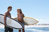 Young couple standing on beach, carrying surfboards, face to face, smiling, side view