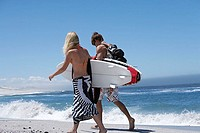 Young couple walking along beach, carrying surfboards under arm, rear view