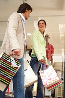 Couple walking past window display in clothes shop, carrying shopping bags, smiling, low angle view