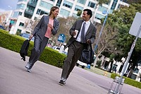 Businessman and businesswoman walking on pavement in city, carrying rucksacks, smiling tilt