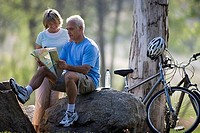 Active senior couple looking at map, sitting on rock beside bicycles, smiling