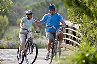 Active senior couple cycling over footbridge, man leaning against woman, laughing