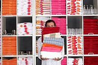 Man shopping in department store, holding large pile of folded towels, face obscured, front view, portrait, shelves in background