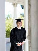 University student in graduation gown and mortar board holding diploma, smiling, portrait