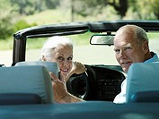 Senior couple sitting in convertible car, looking over shoulder, smiling, rear view, portrait