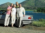 Two senior couples standing beside convertible car near lake, smiling, portrait