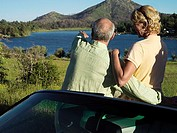 Senior couple standing beside convertible car, man pointing at view of lake, rear view