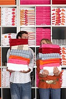 Couple shopping in department store, holding two large piles of towels beside shelf, faces obscuredbackground