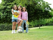 Three girls 7-9 standing on grass in park with frisbee, soccer ball and skipping rope, portrait