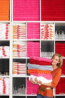 Woman shopping in department store, holding large pile of towels beside shelf, smiling, portrait