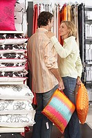 Couple shopping for cushions in department store, woman placing hand on man's shoulder, smiling (thumbnail)
