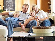 Two generation family sitting on sofa at home, man taking photograph with camera phone, smiling