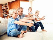 Two generation family sitting on sofa at home, playing with video games console, smiling, side view