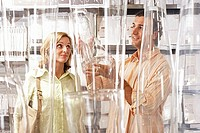 Couple shopping for glass vases in department store, woman raising eyebrows, man smiling