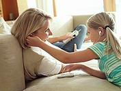 Mother and daughter 6-8 listening to MP3 player on sofa at home, sharing headphones, smiling