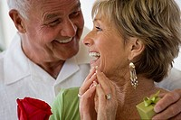 Senior man surprising senior woman with small gift and red rose, laughing and smiling, close-up