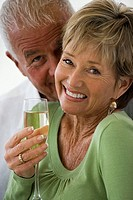 Affectionate senior couple smiling, woman holding glass of champagne, close-up, portrait