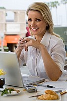 Businesswoman sitting at balcony table with laptop, holding mug of coffee, smiling, portrait