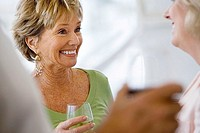 Two senior women talking at social gathering, holding wine glasses, smiling differential focus