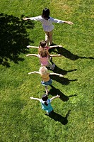 Children 3-5 following teacher in line on grass, arms outstretched, overhead view