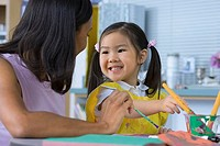 Girl 3-5 painting at desk in classroom, teacher assisting, smiling