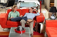 Couple testing new red sofa in furniture store, woman sitting with feet up on man's lap, smiling