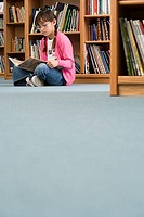 Girl 10-12 in spectacles sitting on floor beside bookshelf in library, reading book, surface level