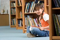 Girl 10-12 sitting on floor beside bookshelf in library, reading book, smiling, side view, portrait