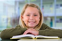 Girl 9-11 reading textbook at desk in classroom, smiling, close-up, front view, portrait