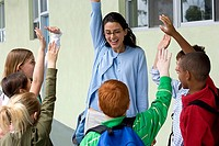 Female teacher talking to children 9-12 outside school, hands raised