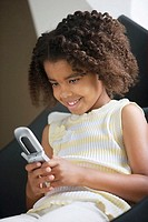 Girl 5-7 text messaging on mobile phone, sitting in chair, smiling, close-up