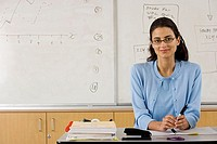 Female school teacher in spectacles sitting at desk in classroom, smiling, portrait
