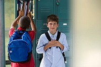 Two boys 10-12 standing beside lockers in school corridor, focus on background