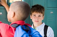 Two boys 10-12 standing beside lockers in school corridor, close-up differential focus