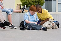 Children 9-11 sitting on wall outside school, two boys sitting on ground playing video game