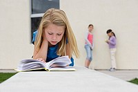 Girl 9-11 reading book outside school, two girls talking beside wall, focus on foreground